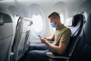 man wearing a face mask on an airplane