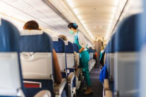 Flight attendant in facial mask protection from covid-19 serves