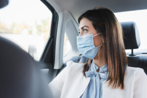 woman riding in a cab with a mask on