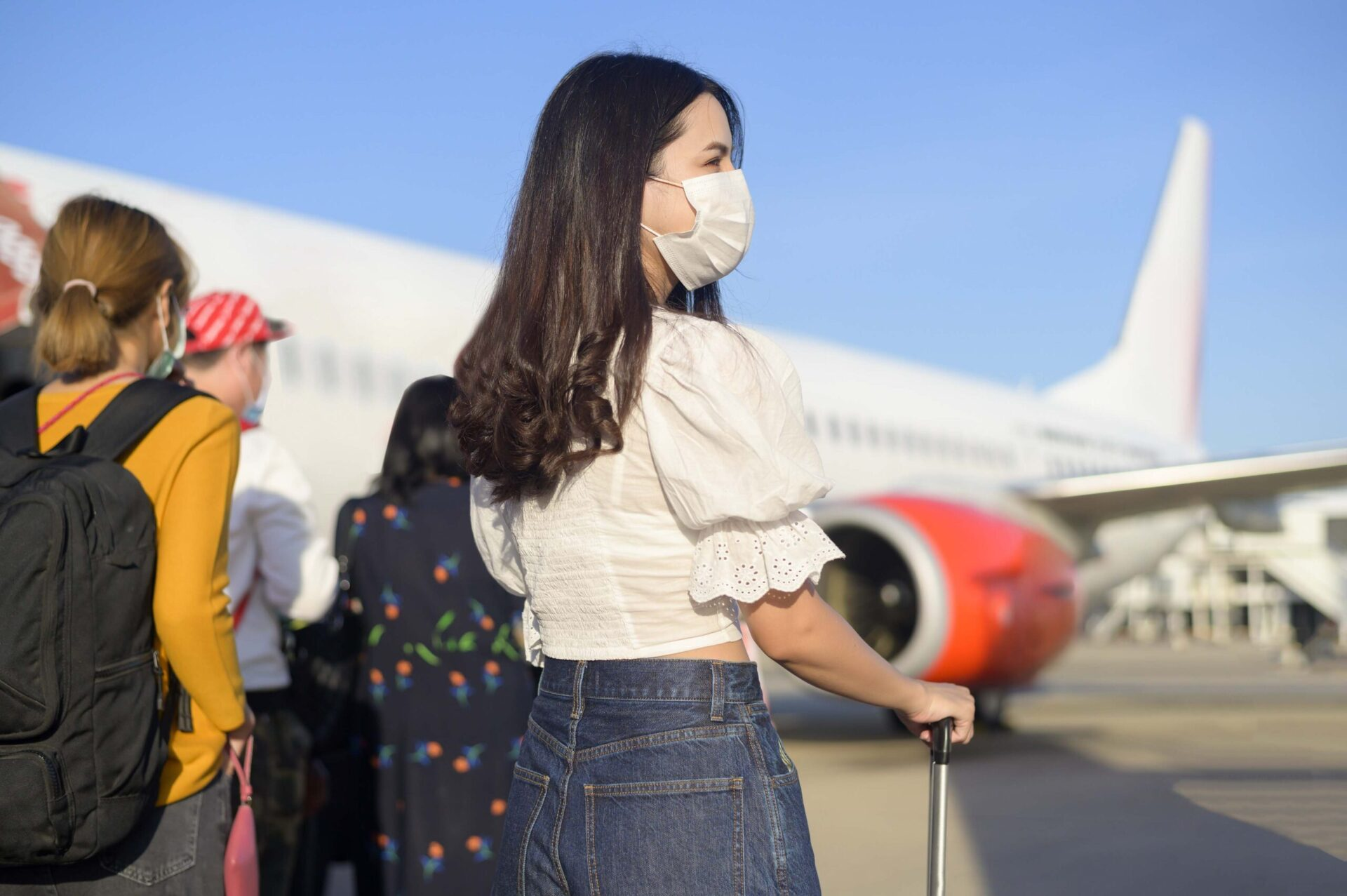 young woman getting on a plane and wearing a face mask